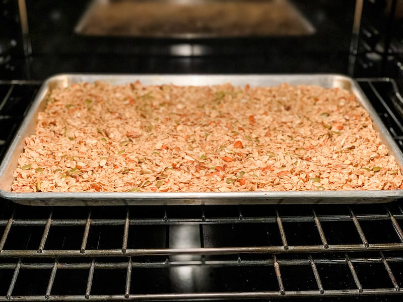 Bake homemade granola on a large metal baking pan